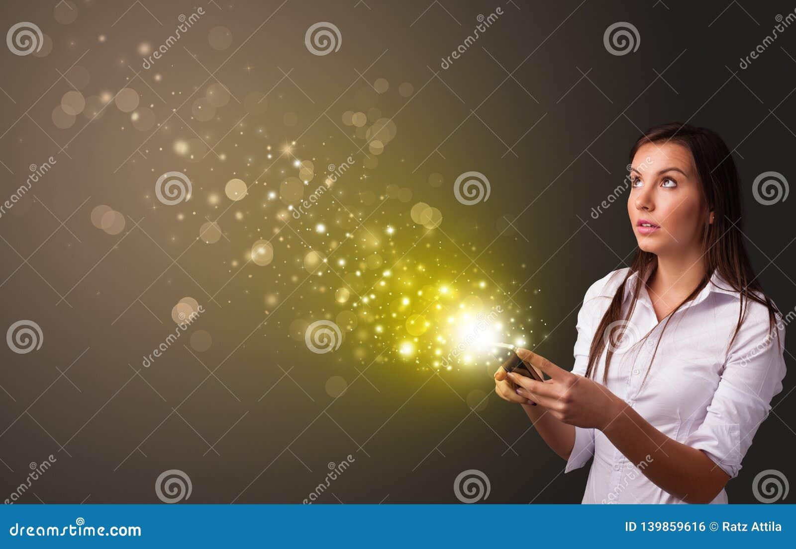 Usando el teléfono con concepto chispeante del oro
