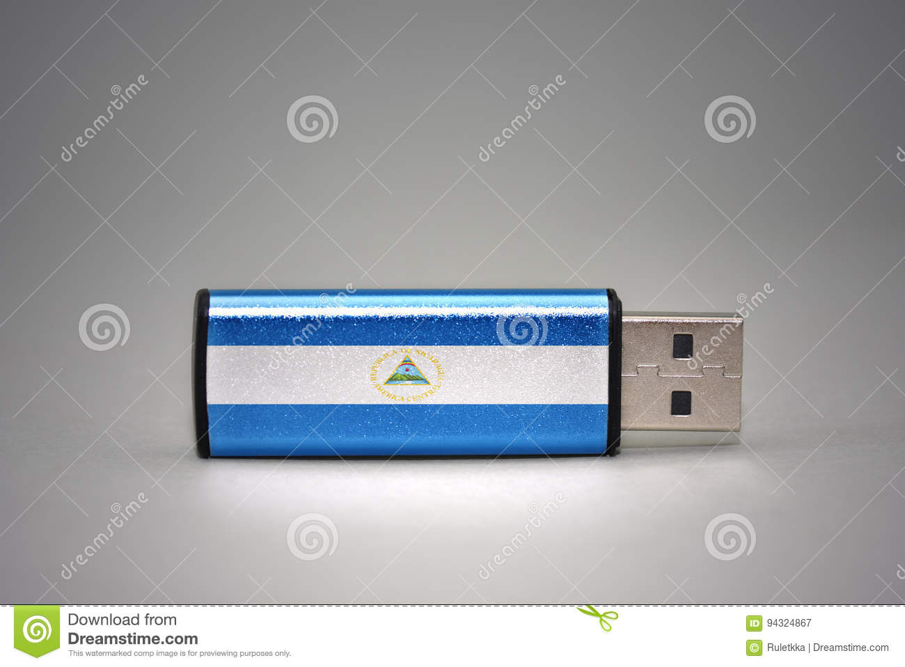 Usb flash drive with the national flag of nicaragua on gray background.