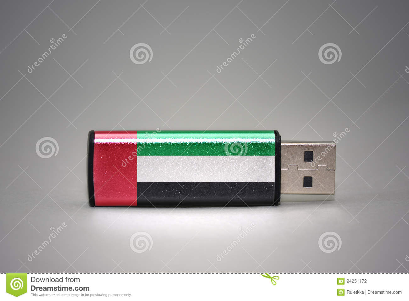Usb flash drive with the national flag of united arab emirates on gray background.