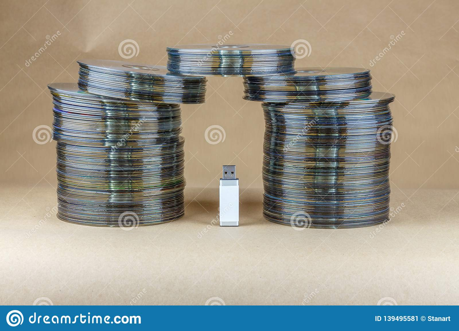 USB Universal Serial Bus stick is surroundet between a stack of cd compact disc and dvd digital versatile optical disc