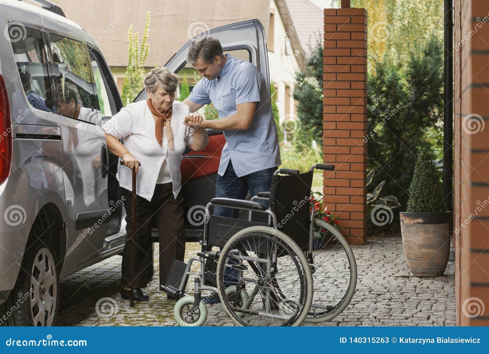 Uscire senior della donna dell automobile con l aiuto di un infermiere