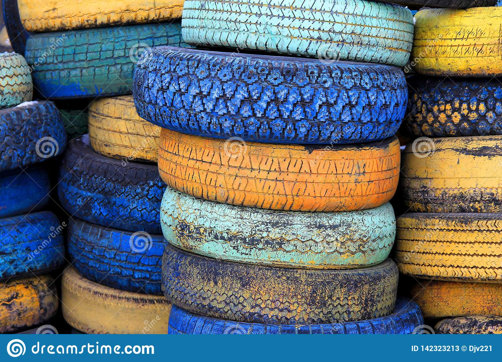 Car tires painted in different colors are stacked on top of each other