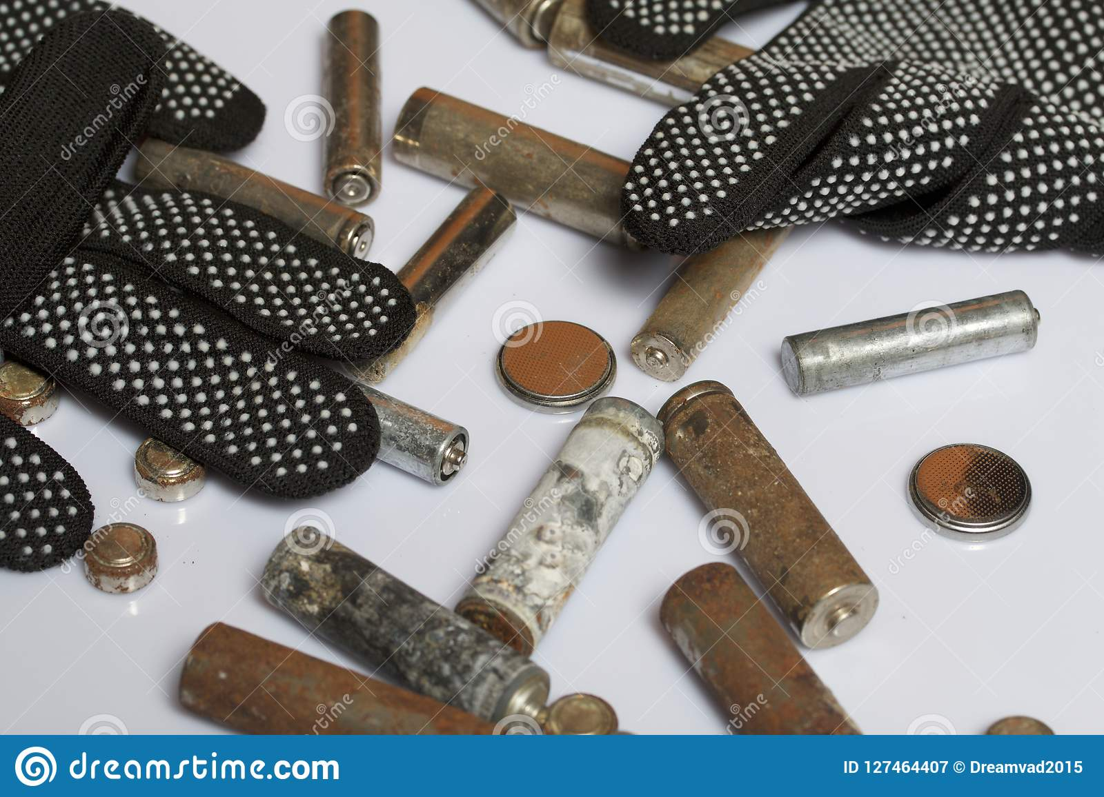 Used finger-wound batteries covered with corrosion. They lie on a wooden box. Next working gloves. Recycling.