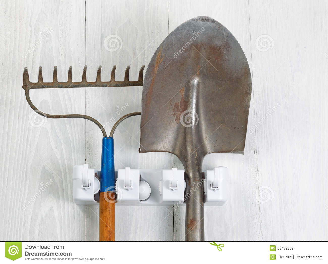 Used Garden Tools Hanging From Rack On White Wooden Boards