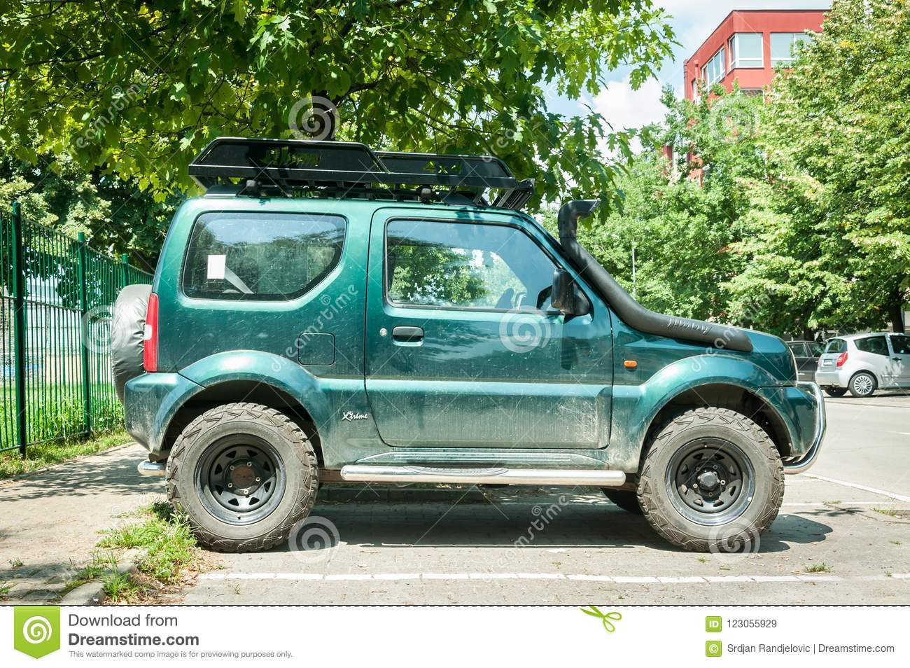 Used Green Dirty Suzuki Jimny 4x4 SUV Off Road Car Parked On