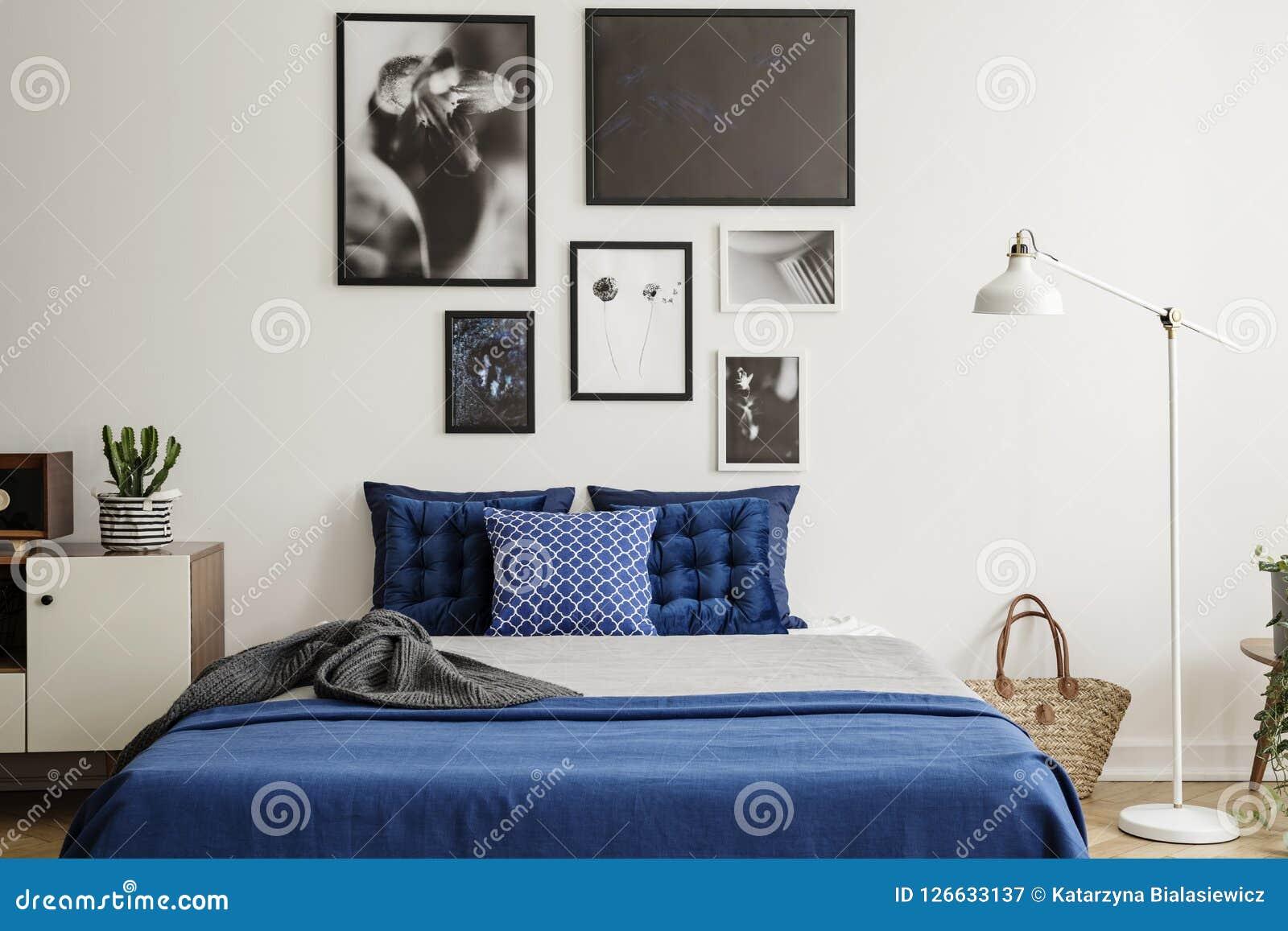 Usine Sur Le Coffret à Côté Du Lit De Bleu Marine Dans Lu0027intérieur De  Chambre à Coucher Avec La Lampe Blanche Et La Galerie Vrai Concept De Photo