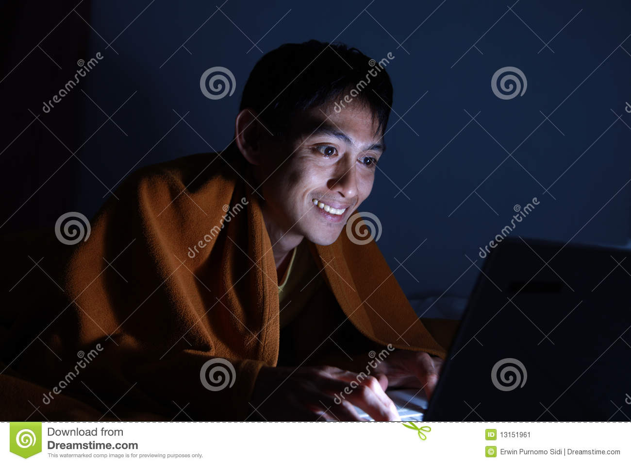 Using laptop on bed at night