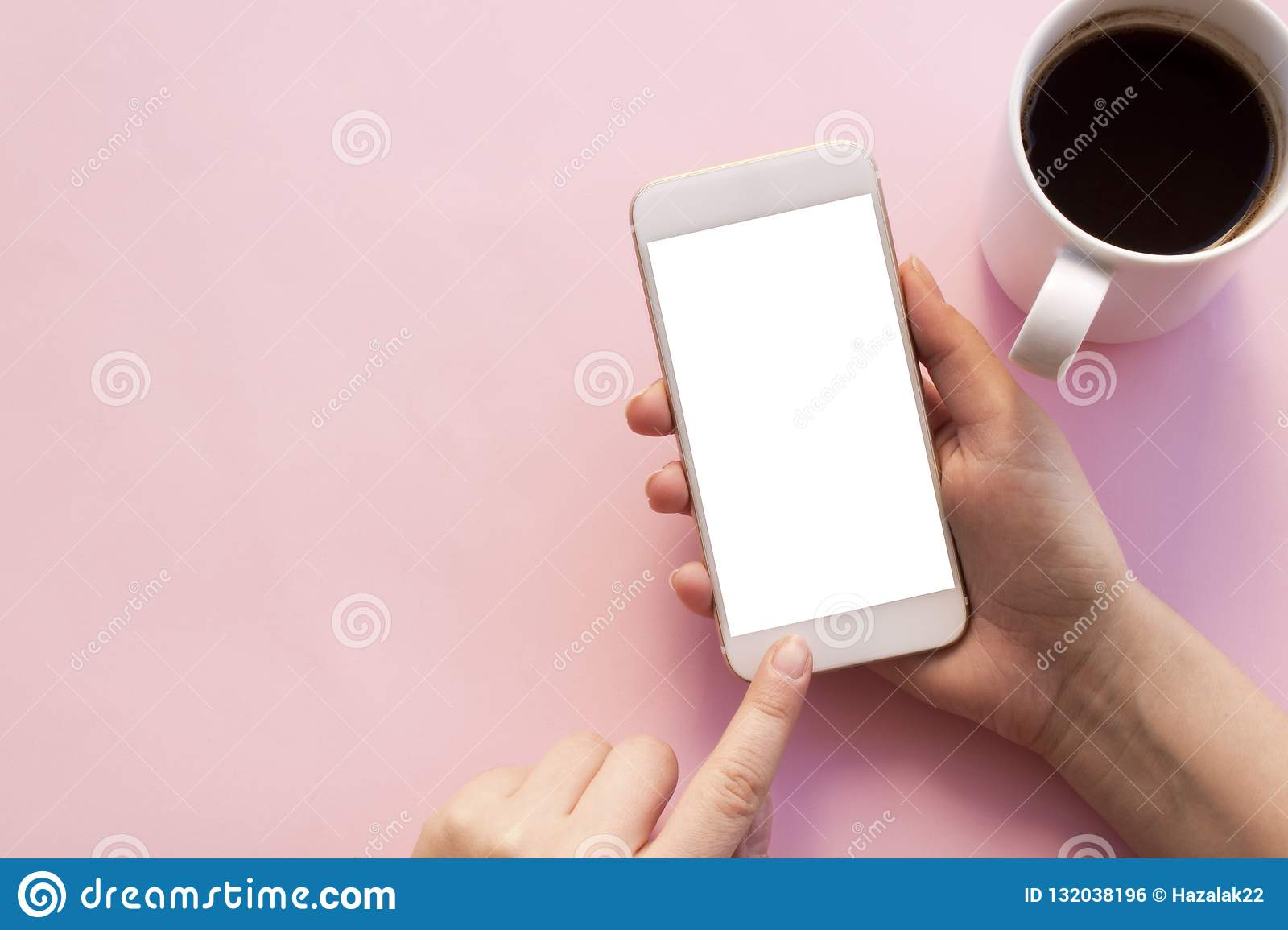 Using mobile phone holding coffee cup.
