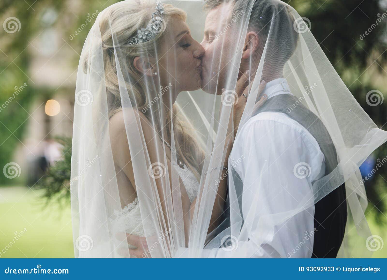 588939d0062 Casese nuevamente los pares están abrazando en un beso, debajo del velo de  las novias
