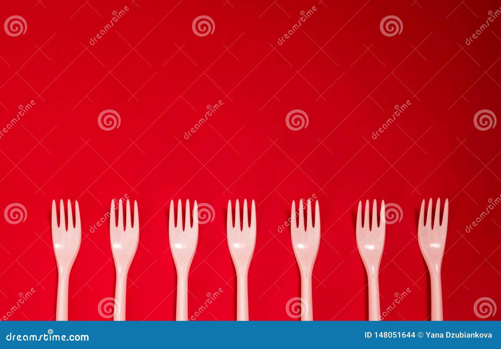 Ustensiles jetables en plastique de fourchettes sur un fond rouge