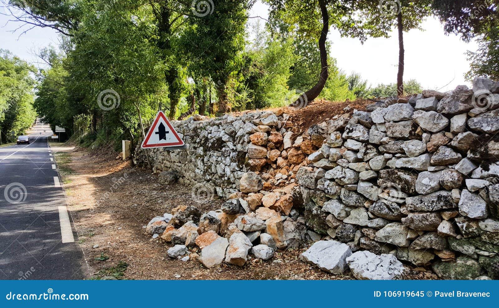 Uszkadzająca stara ściana obok drogi z kamieniami