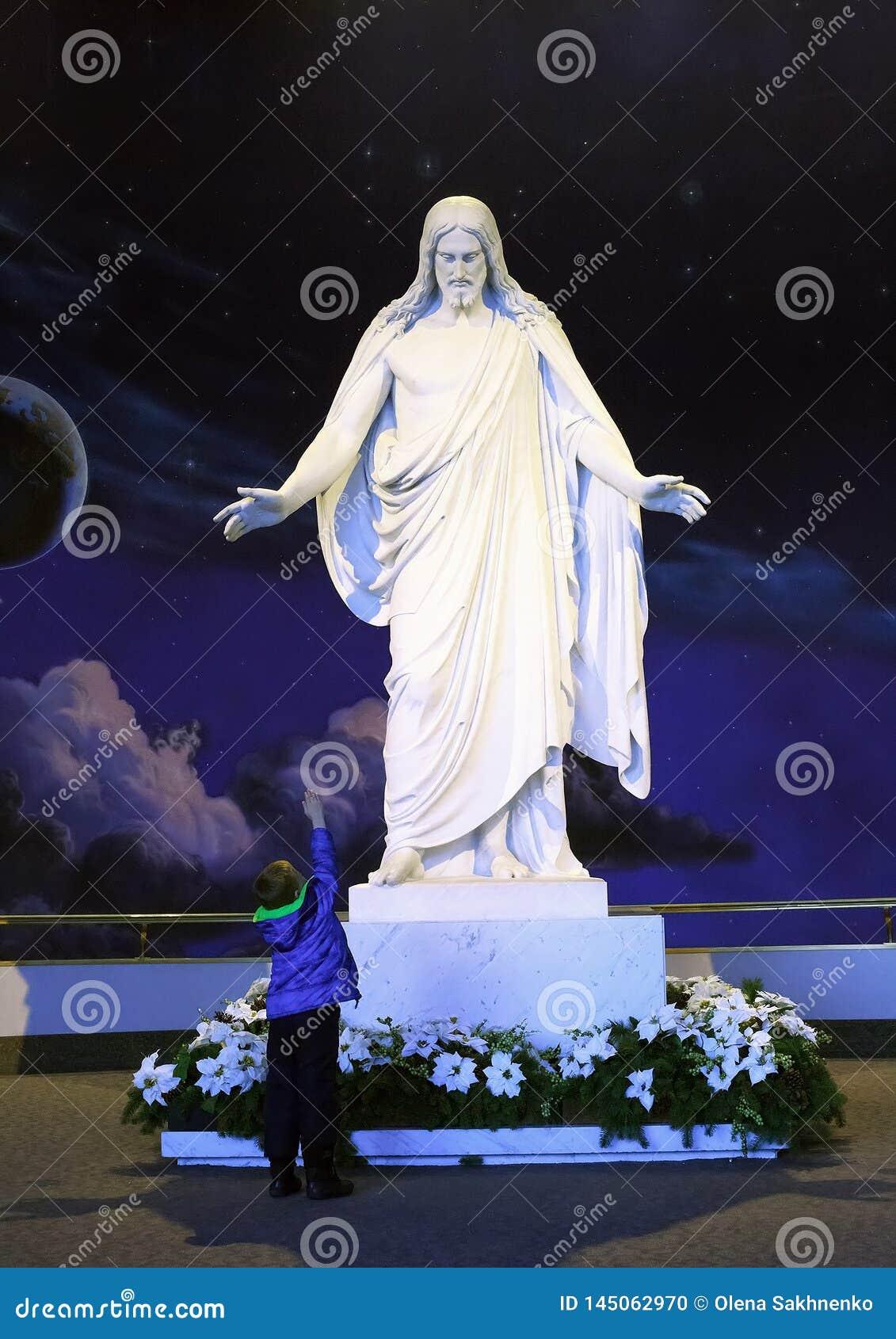 Utah, de V.S. - 21 December, 2016: een marmeren standbeeld van Jesus Christ met open wapens en een jongen die uit zijn hand aan J