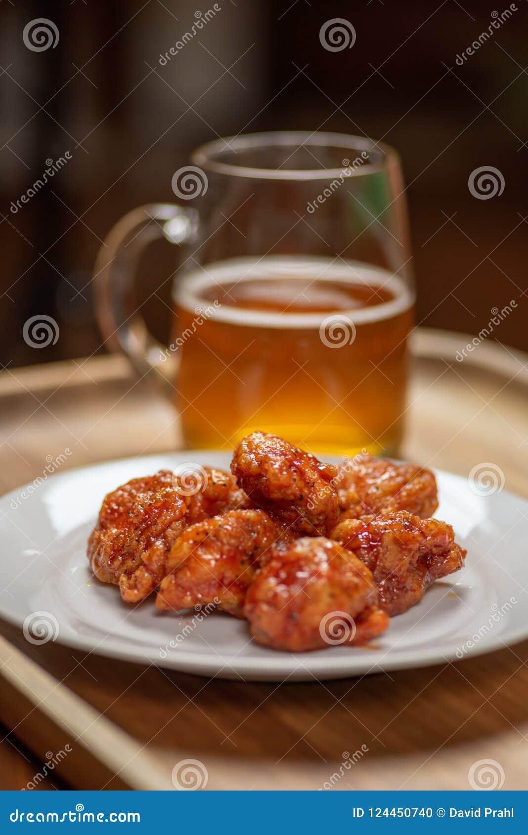 Utan ben kryddiga varma buffelvingar på plattan med exponeringsglas rånar av öl