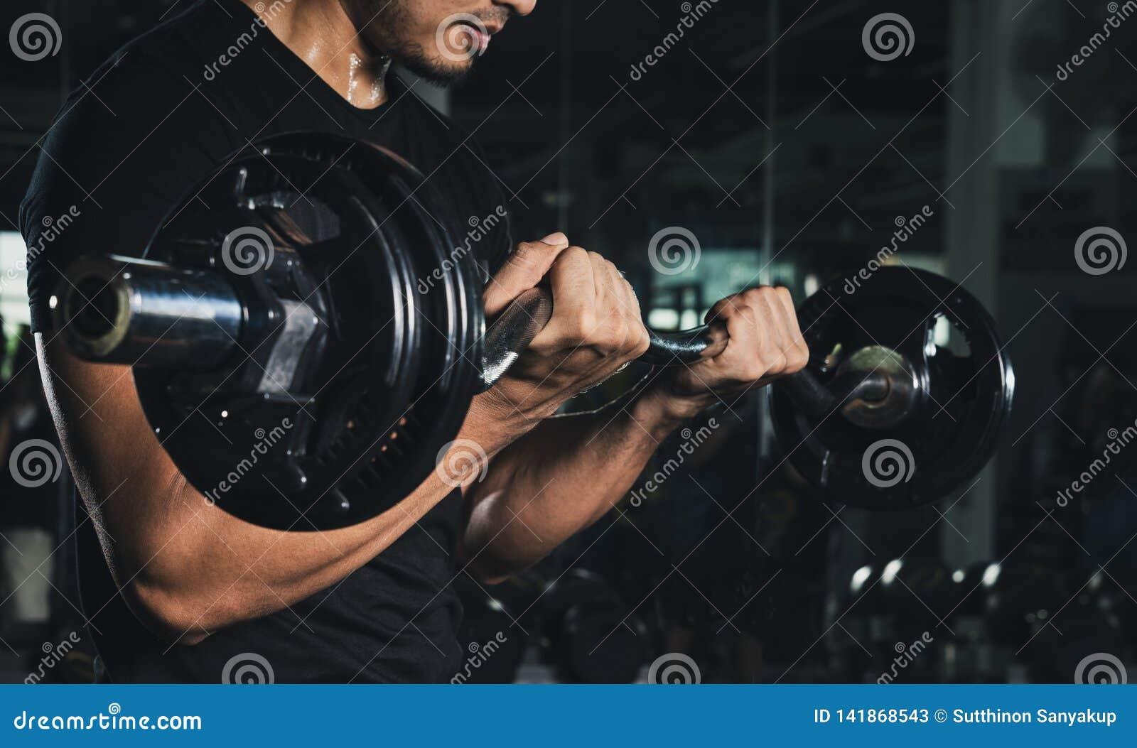 Utbildning med skivstången, idrotts- shirtless ung sportman - konditionmodell med skivstången i idrottshallen, stilig weightlifte