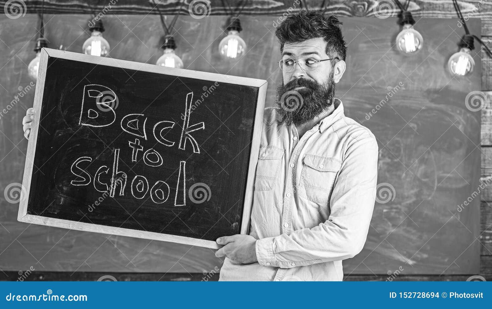 Utbildning och studerabegrepp Mannen med sk?gget och mustaschen p? gladlynt framsida v?lkomnar studenter, svart tavla p? bakgrund