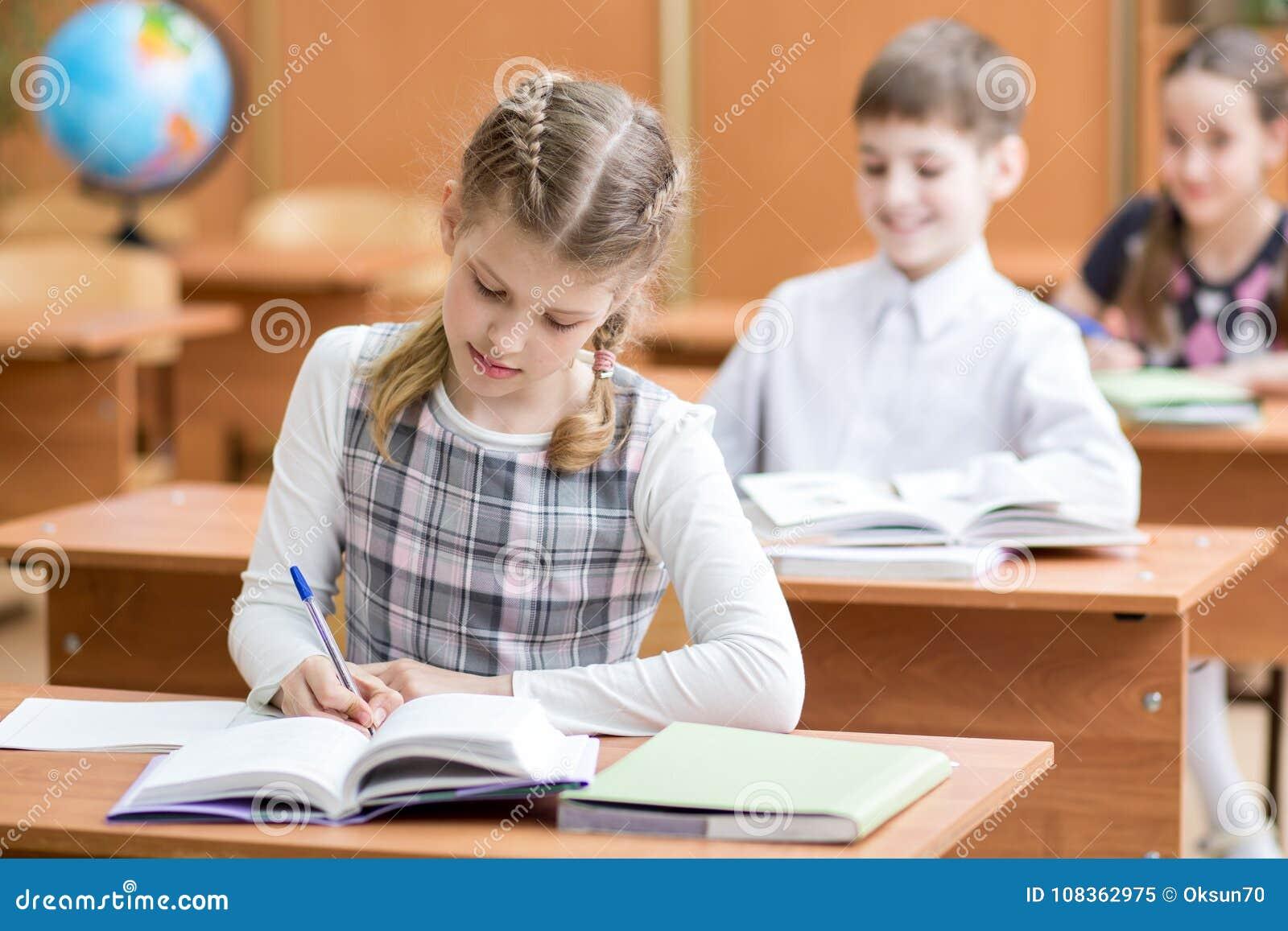 Utbildning, skola, lära och barnbegrepp - grupp av skolaungar med pennor och läroböcker som skriver provet i klassrum