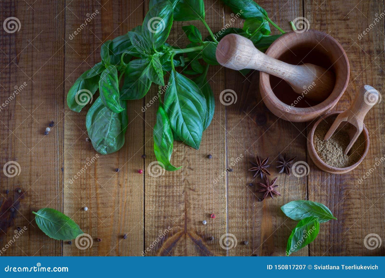 Utensilios de la cocina para las especias Albahaca y especias frescas en la tabla
