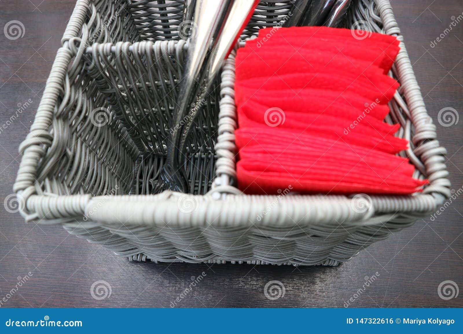 Utensilios de servicio de la cocina en una cesta de mimbre con las bifurcaciones y los cuchillos en la tabla