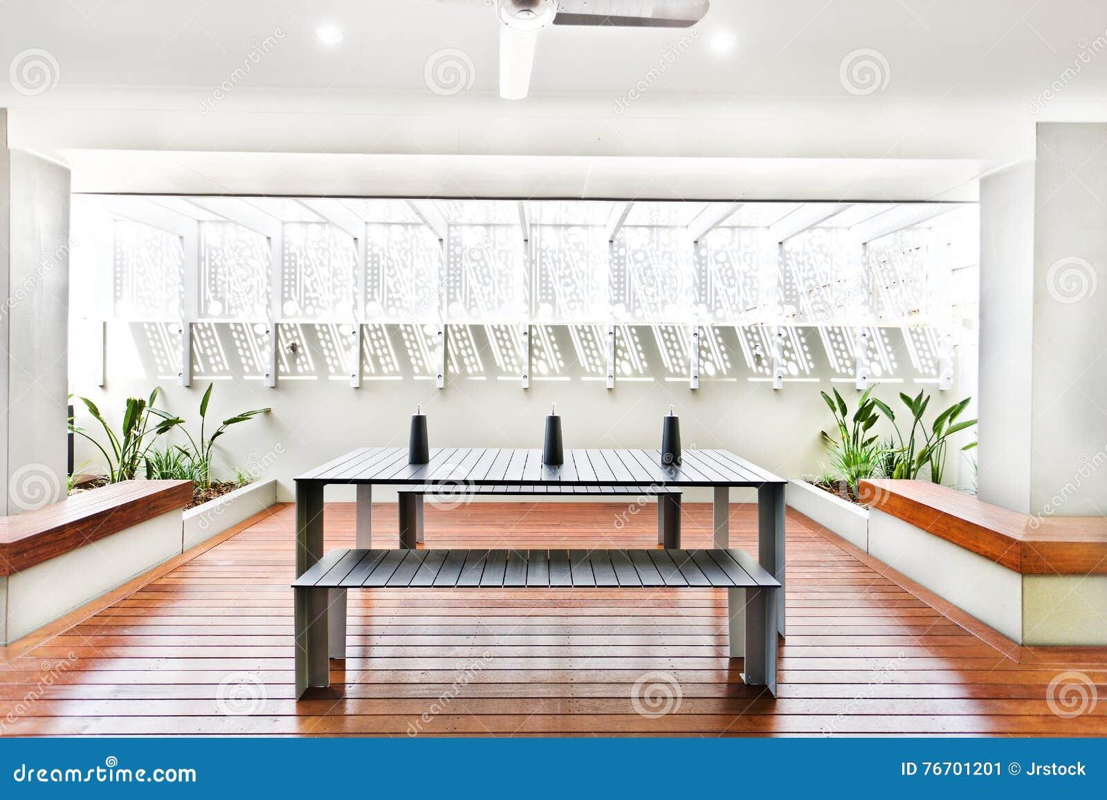 Uteplatsområde med trägolvet inklusive en tabell och bänkar
