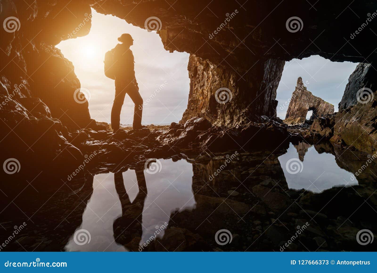 Utforskare i en grotta på solnedgången i den Portizuelo stranden, Asturias kust, norr Spanien