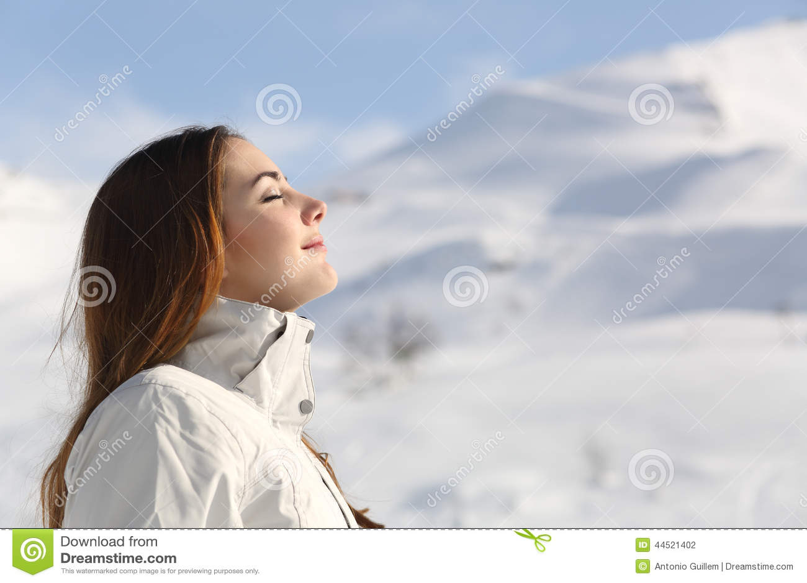 Utforskarekvinna som andas ny luft i vinter i ett snöig berg