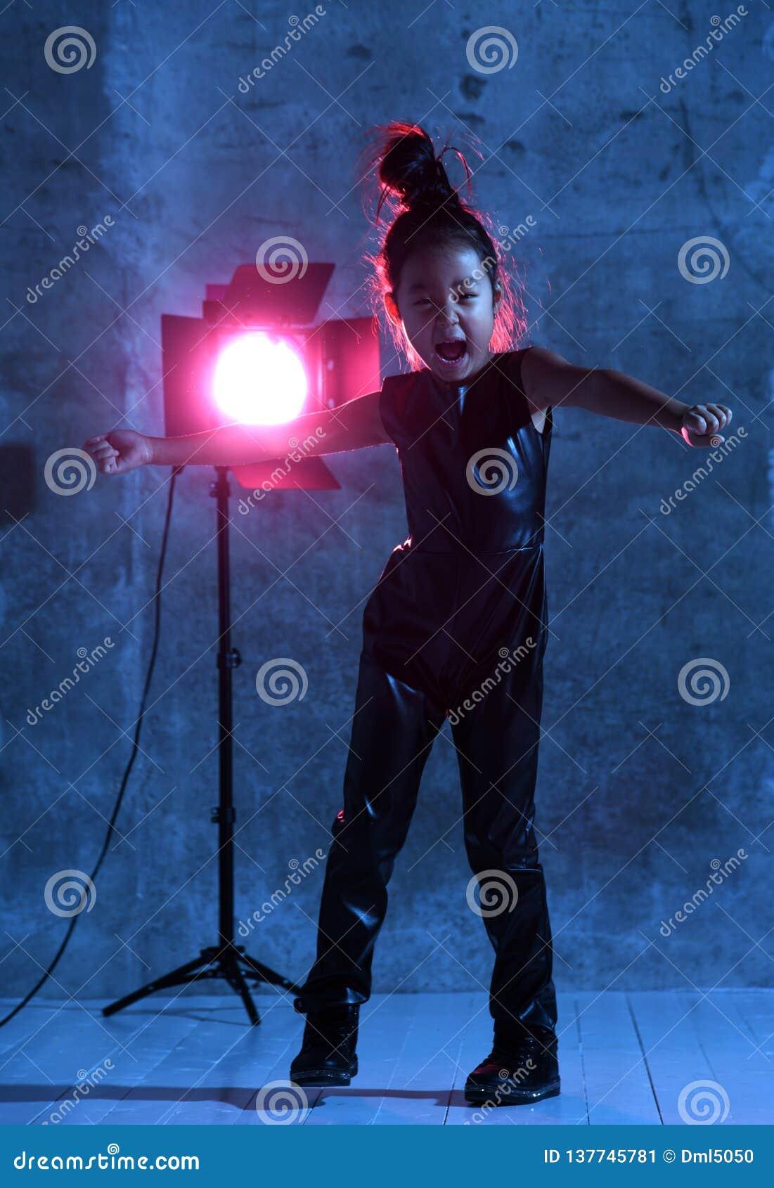 Utgör den asiatiska modellflickan för högt mode med den färgrika studiostrålkastaren gladlynt