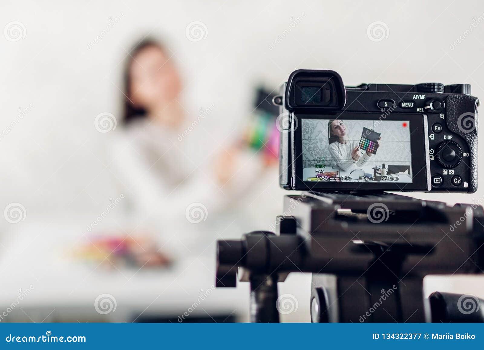 Utgör yrkesmässig skönhetvlogger för den unga kvinnan eller bloggerinspelning den orubbliga användande kameran och tripoden
