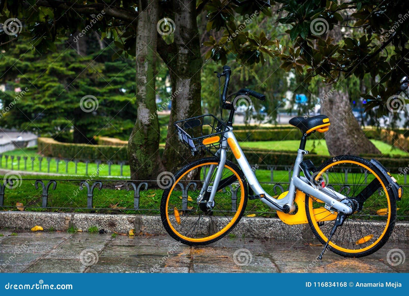 Uthyrnings- offentlig cykel som parkeras på en regnig dag