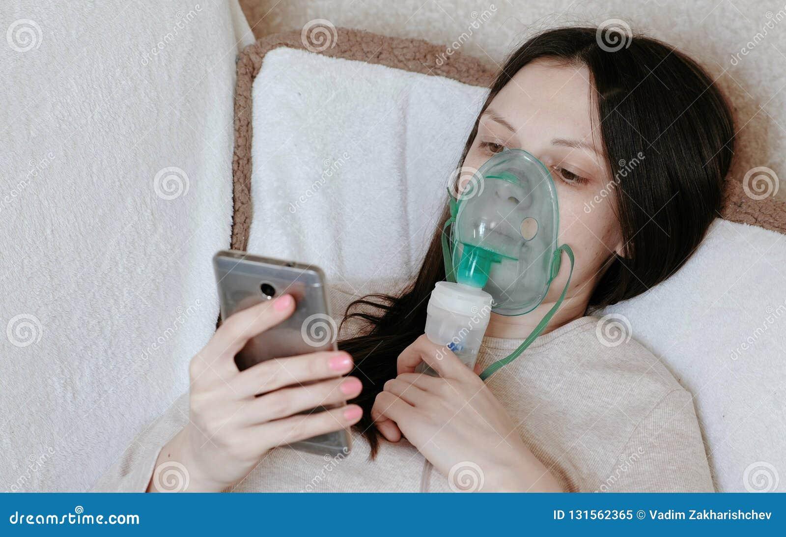 Utilice el nebulizador y el inhalador para el tratamiento Mujer joven que inhala a través de la máscara del inhalador que miente