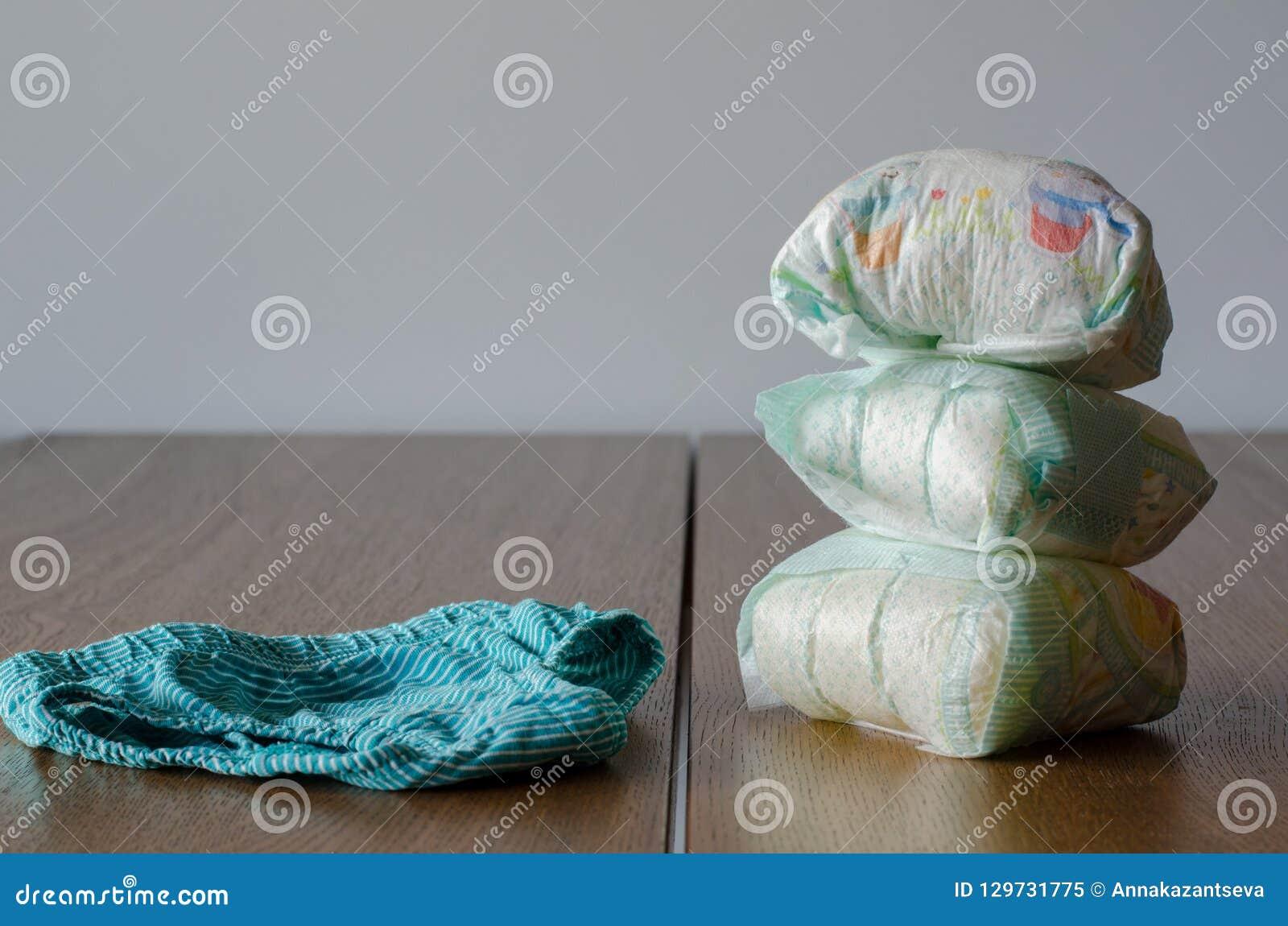 A utilisé des couches-culottes et nettoie la culotte des enfants sur un backg en bois de table