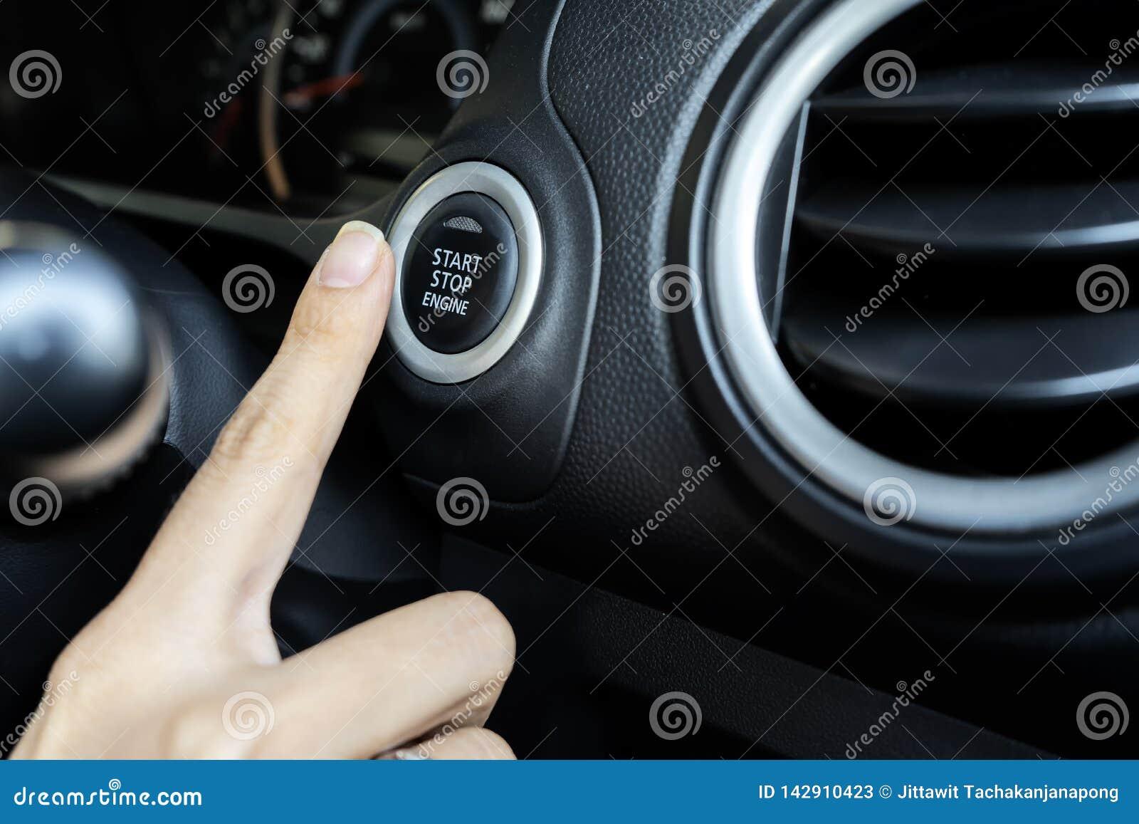 Utilisant le bouton poussoir pour mettre en marche et arrêter le moteur, le doigt de la femme enfonce
