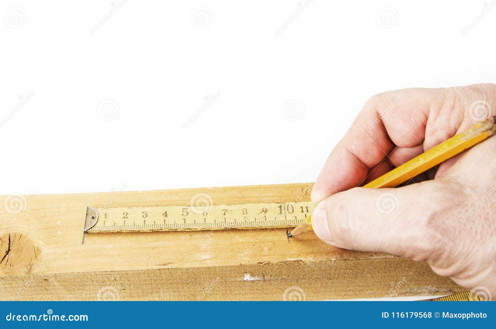 Utilisant le vieux mètre se pliant jaune pour mesurer le bois pour couper