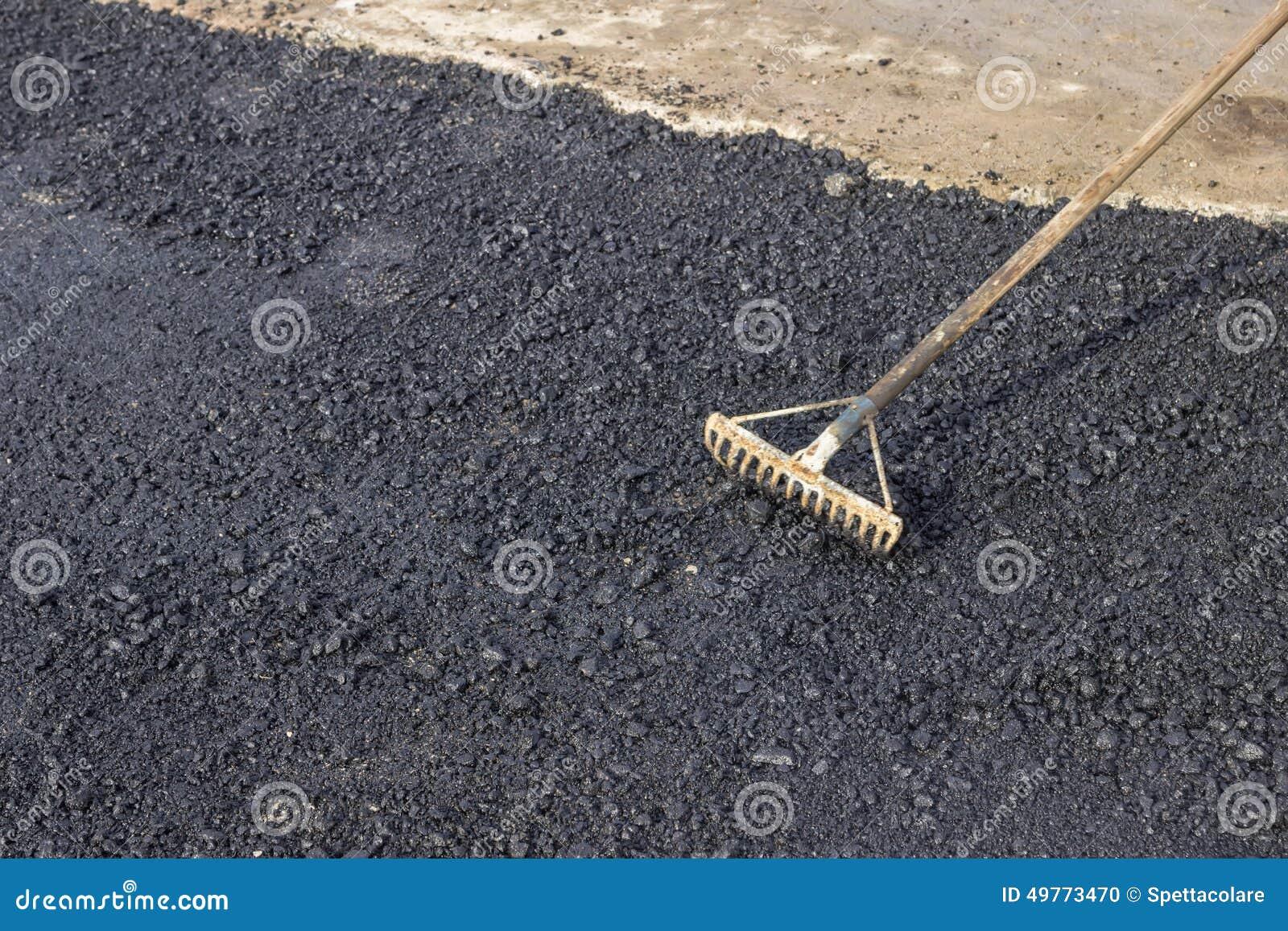 Utilisant un r teau pour niveler le trottoir d 39 asphalte photo stock image 49773470 - Niveler un terrain pour pelouse ...
