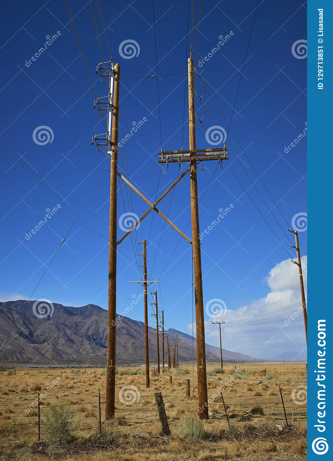 Utility Poles In Desert  Clear Blue Sky And Mountains In Distance