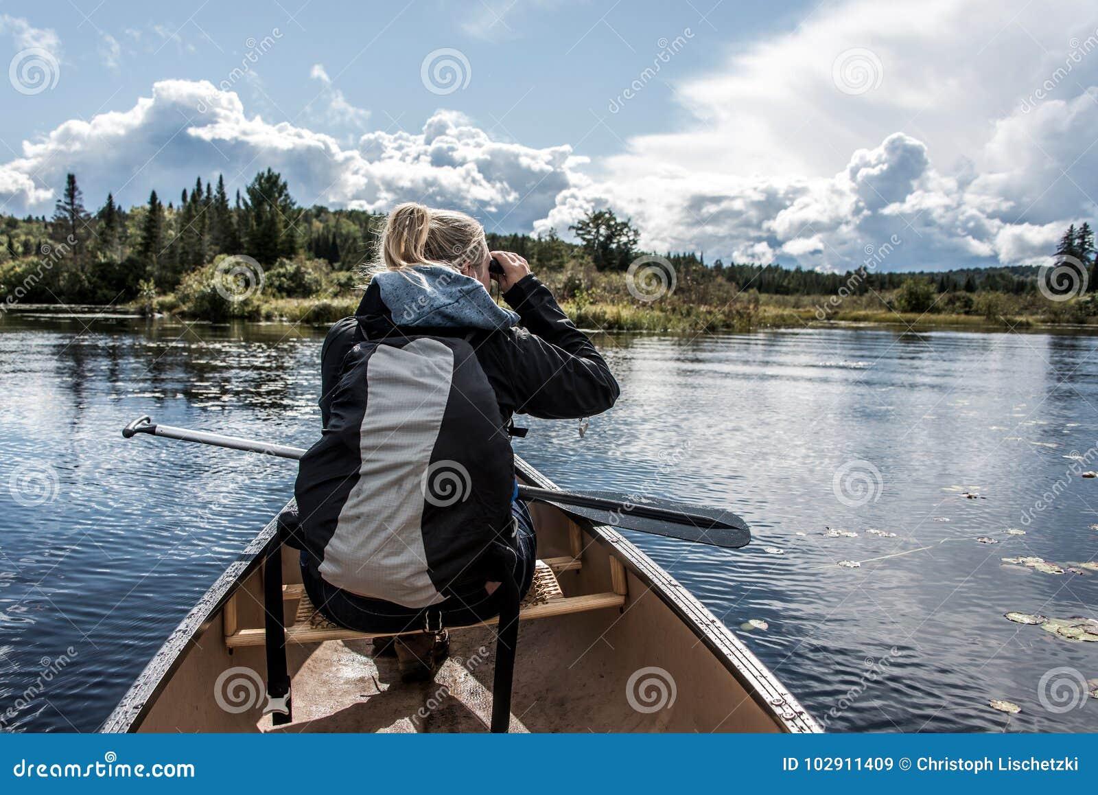 Utilizzare della ragazza binoculare su un lago canoe di due fiumi nel parco nazionale del algonquin in Ontario Canada il giorno n