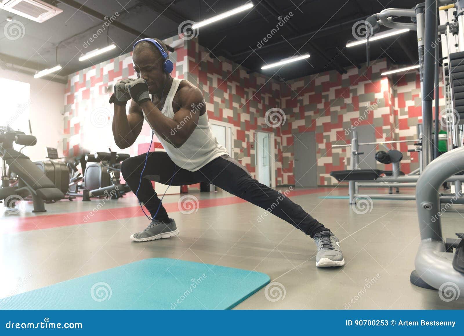 Utmärkt sträcka Sidosikt av den unga stiliga mannen i sportswearen som gör sträckning på idrottshallen