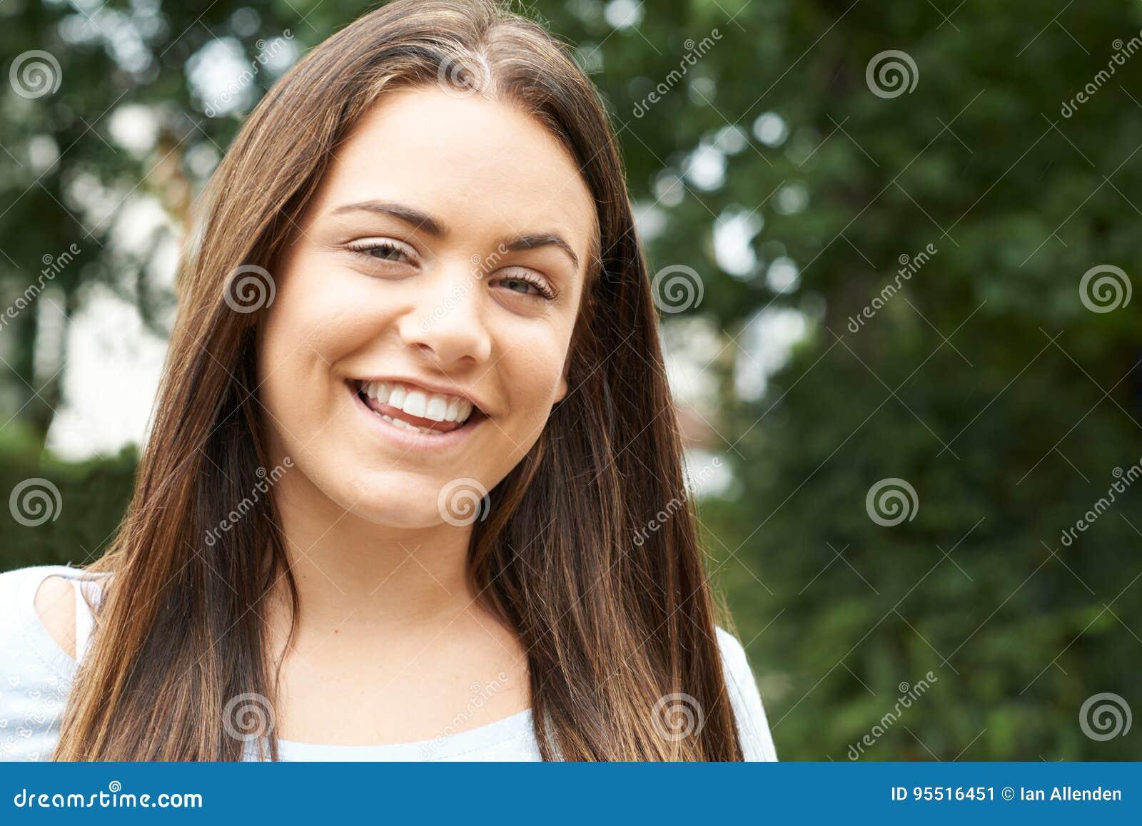 Utomhus- Head och skuldrastående av att le den tonårs- flickan