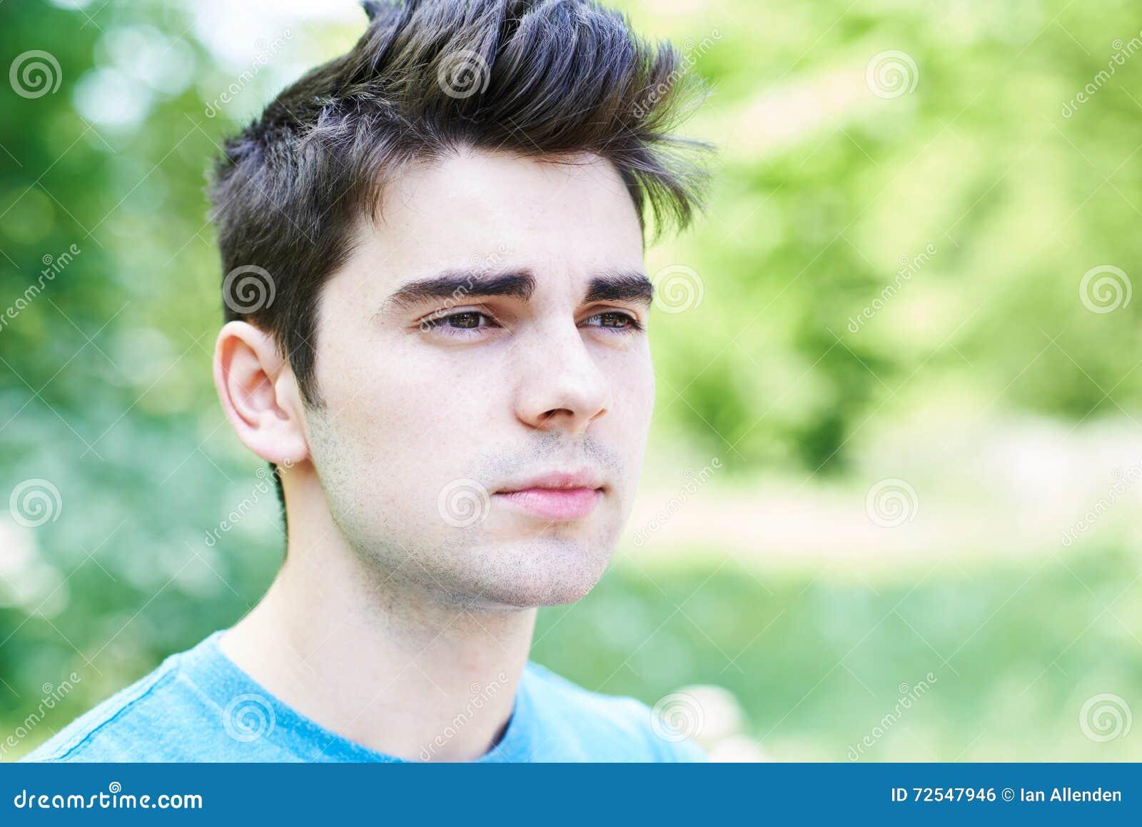 Utomhus- Head och skuldrastående av den allvarliga unga mannen
