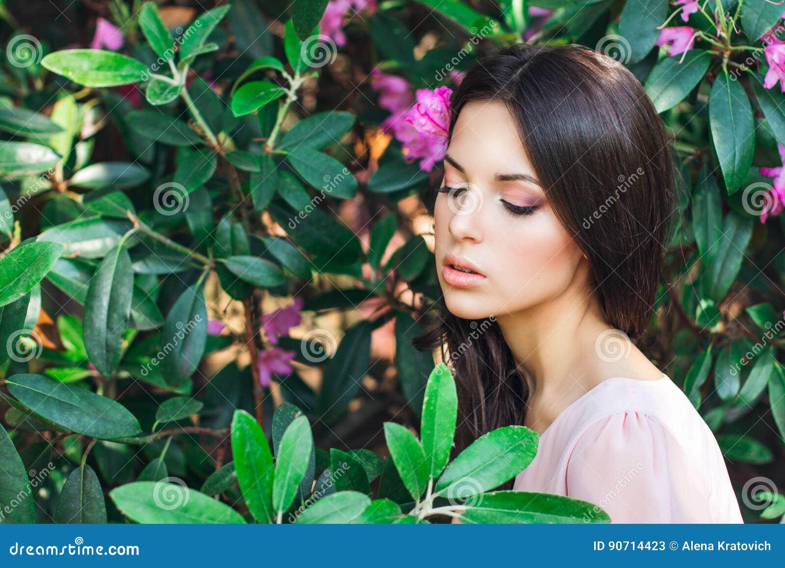 Utomhus- modefoto av den härliga unga kvinnan som omges av blommor fjäder för blomma för dof för azaleablomningclose grund upp