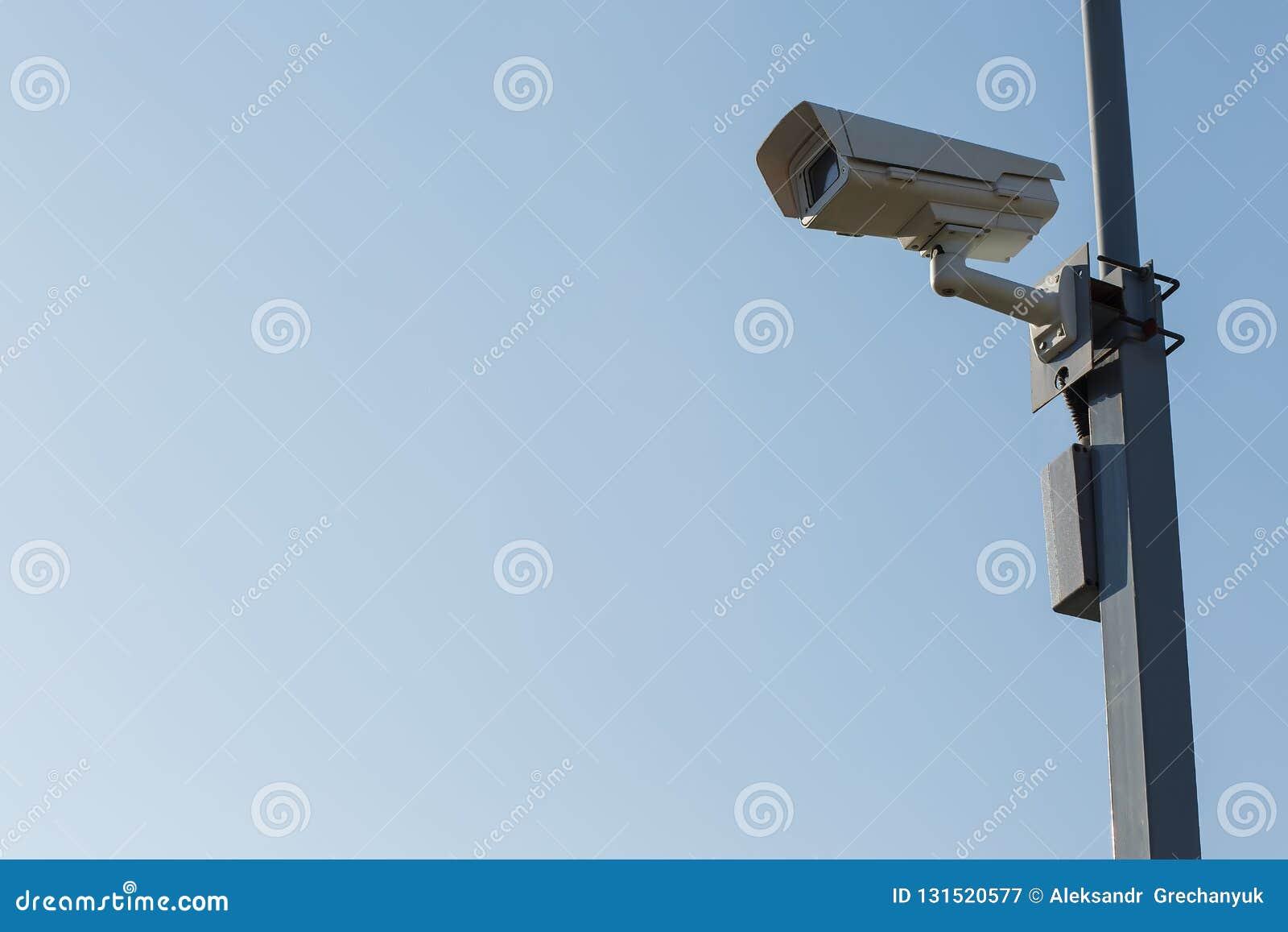 Utomhus- säkerhetskamera på bakgrund för blå himmel