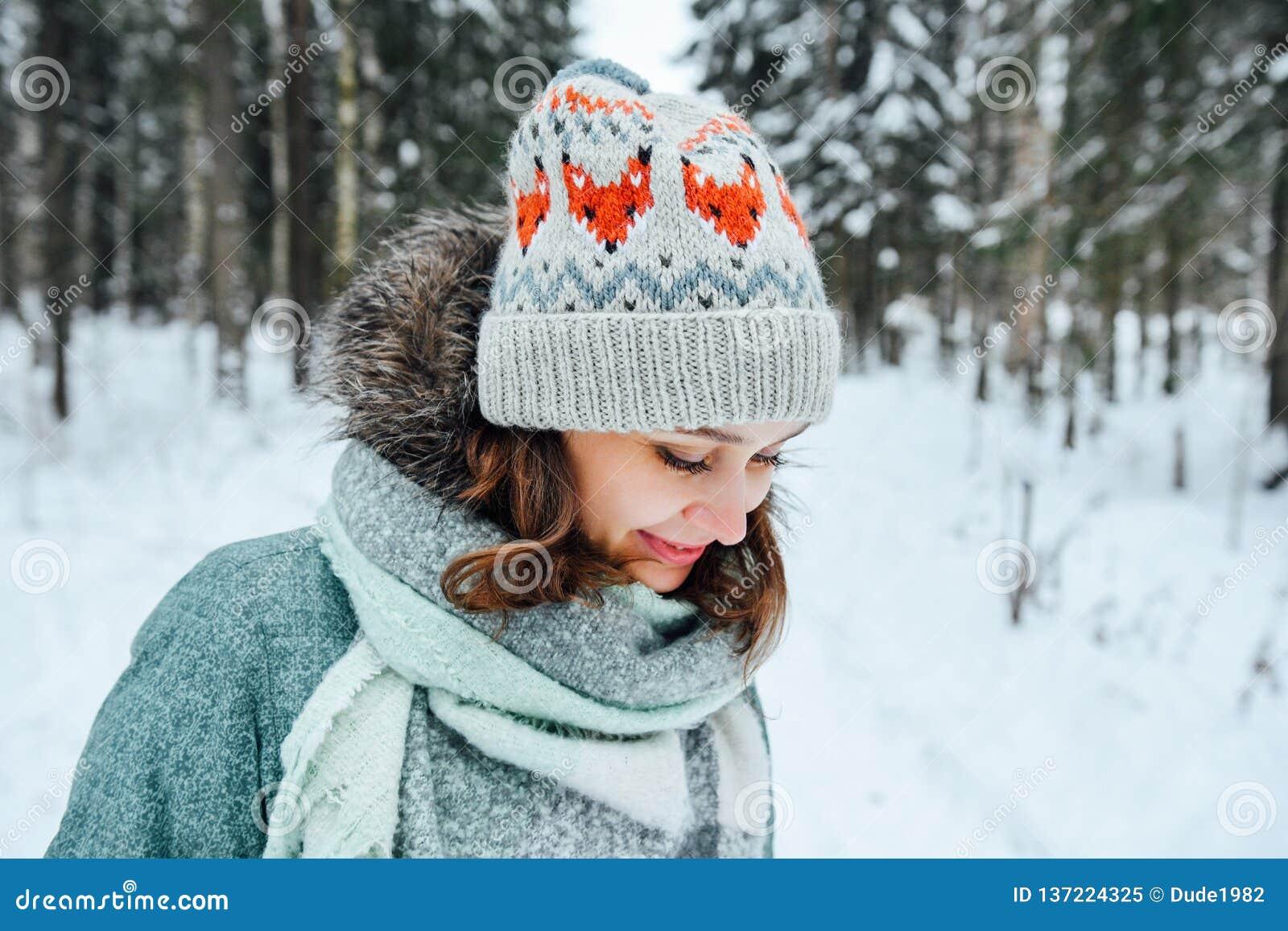 Utomhus- slut upp ståenden av den unga härliga lyckliga flickan, bärande stilfull stucken vinterhatt