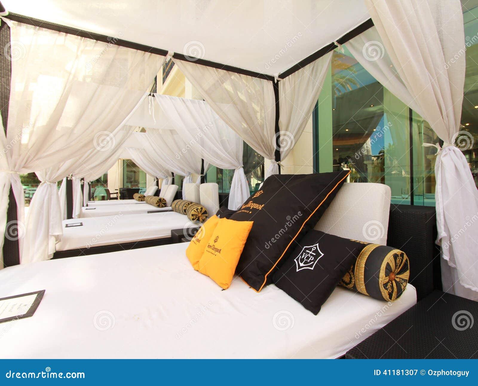 Utomhus  säng i en cabana bredvid en semesterortpöl redaktionell ...