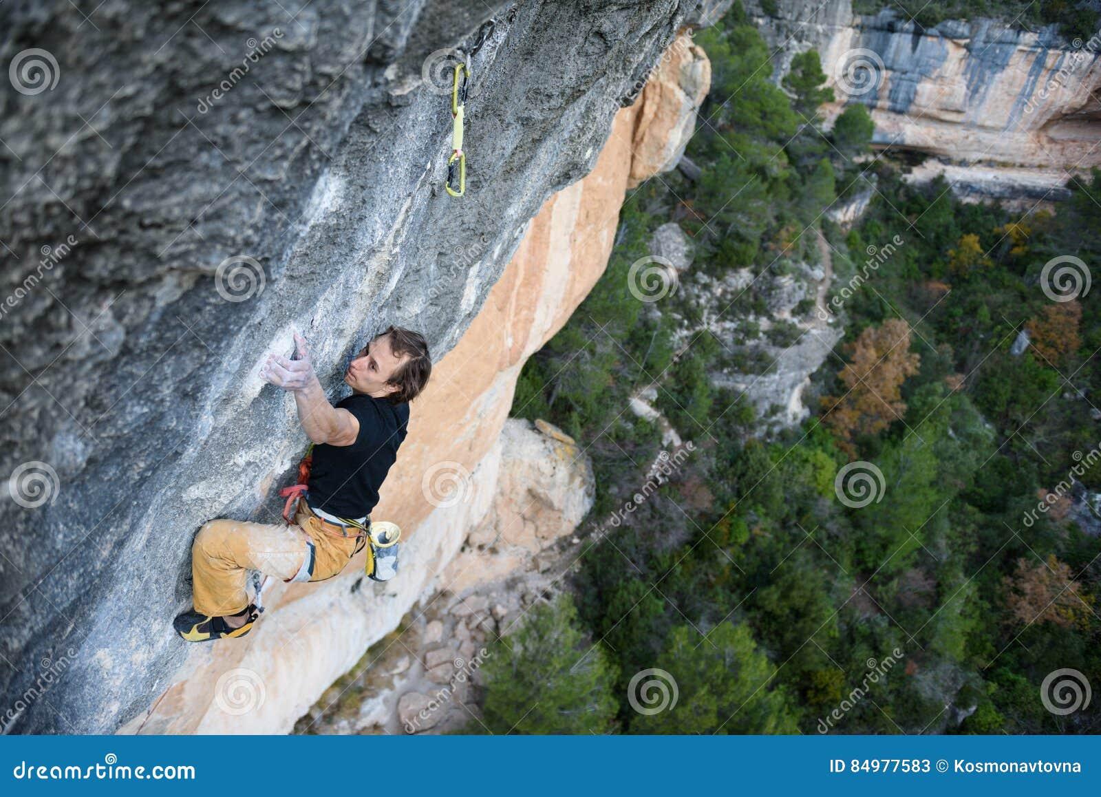 Utomhus- sport Vagga klättraren som stiger en utmanande klippa Extrem sportklättring