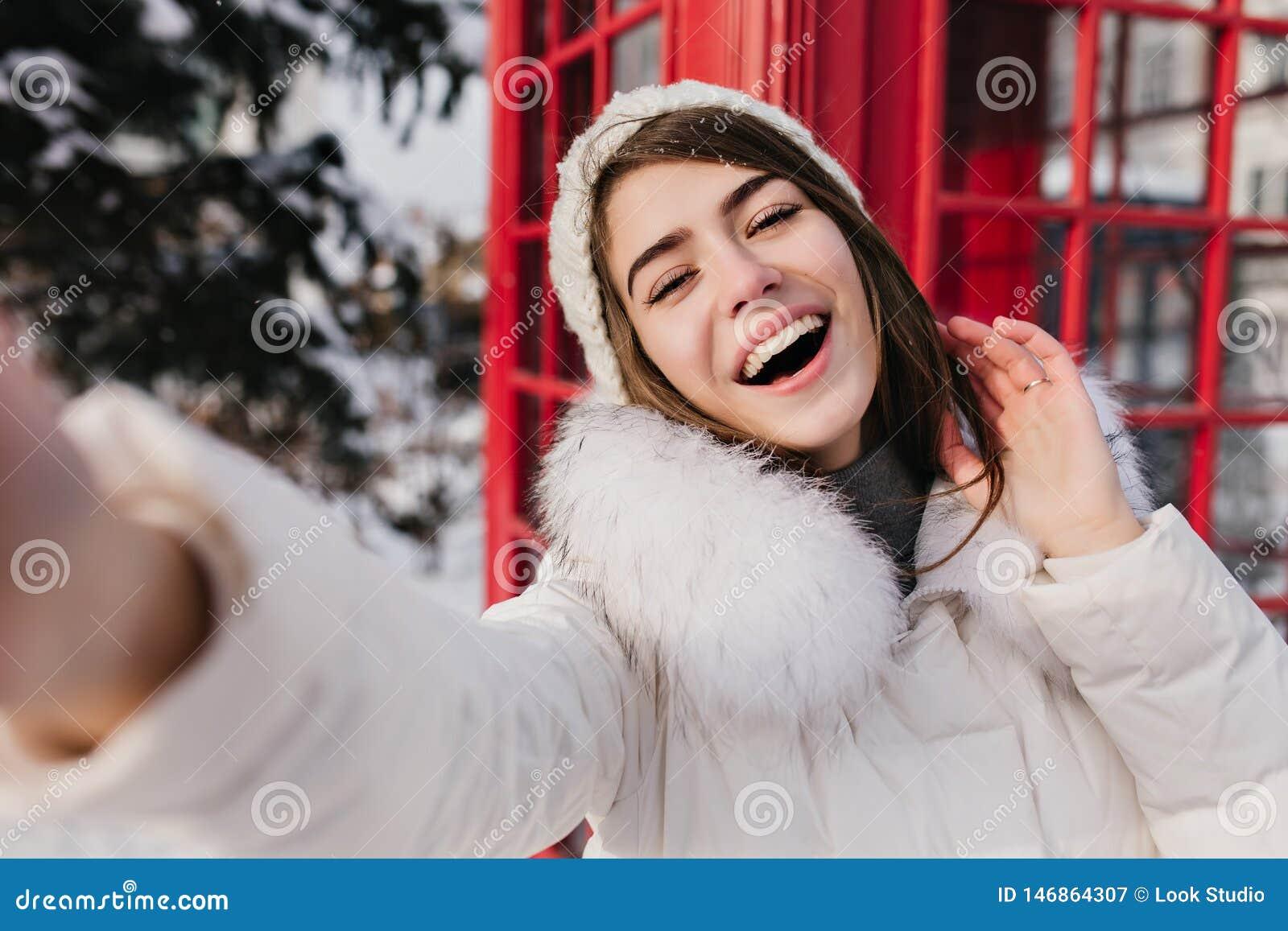 Utomhus- stående av den gulliga kvinnan med det lyckliga leendet som gör selfie i London under vintersemester Förtjusande flicka