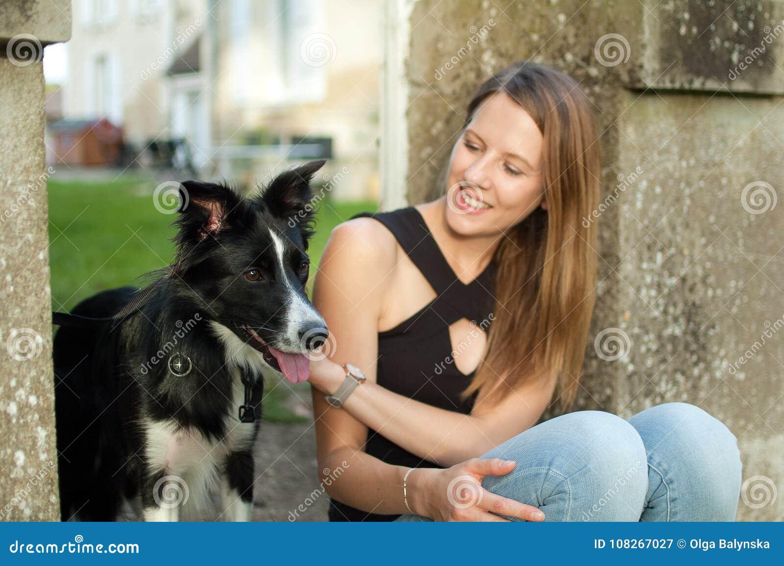 Utomhus stående av den nätta attraktiva flickan som spenderar tid med hennes svarta hund under sommardag