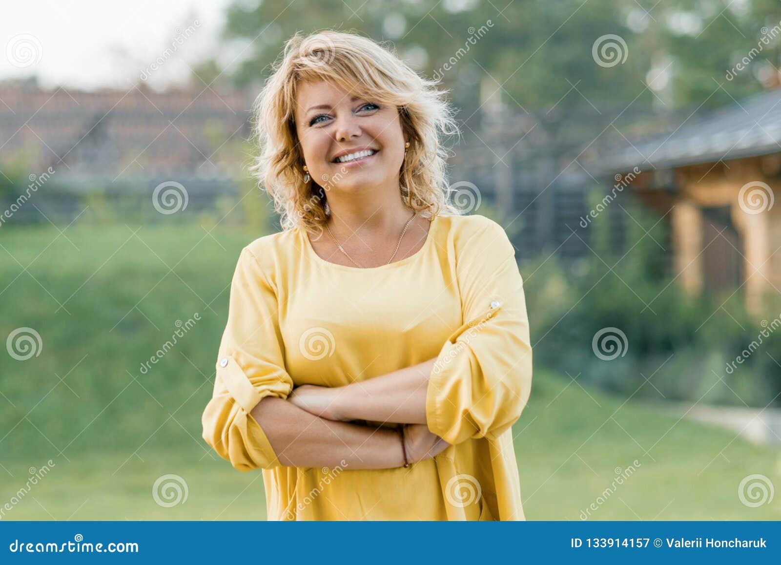 Utomhus- stående av den positiva säkra mogna kvinnan Le den kvinnliga blondinen i en gul klänning med armar som korsas nära huset