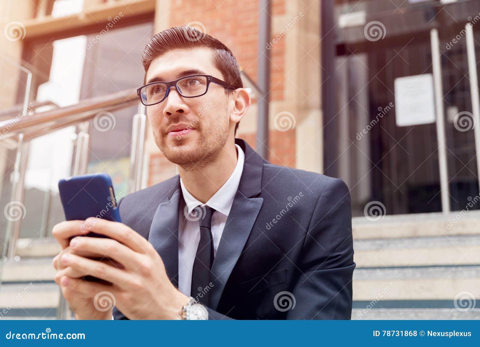 Utomhus- stående av den stiliga affärsmannen