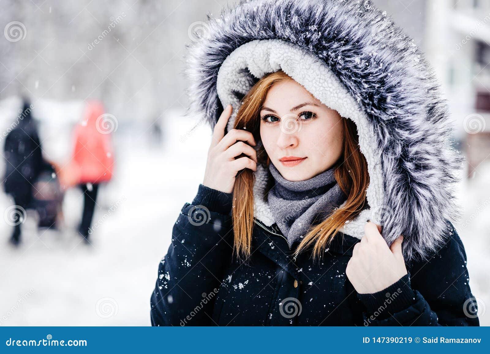Utomhus- stående av den unga härliga flickan som bär i svart omslag med en huv Modell som poserar i gata Begrepp f?r vinterferier