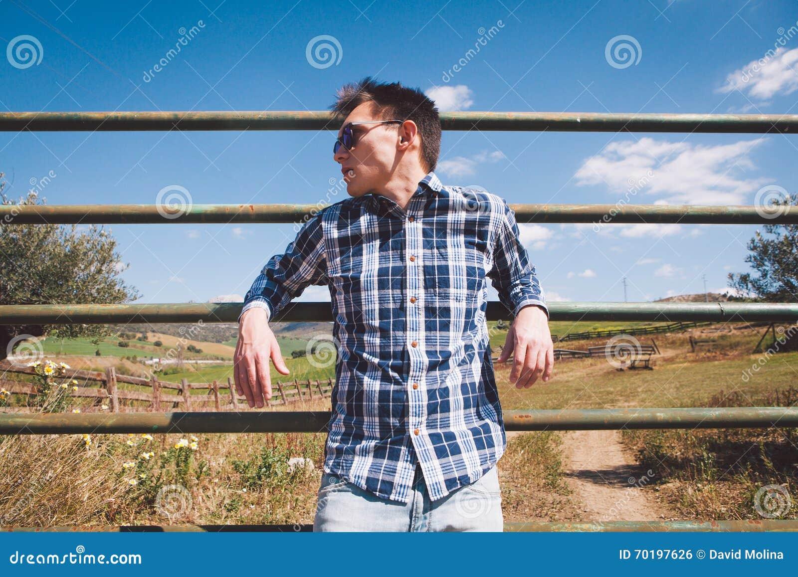 Utomhus stående av den unga mannen i solglasögon på bygden