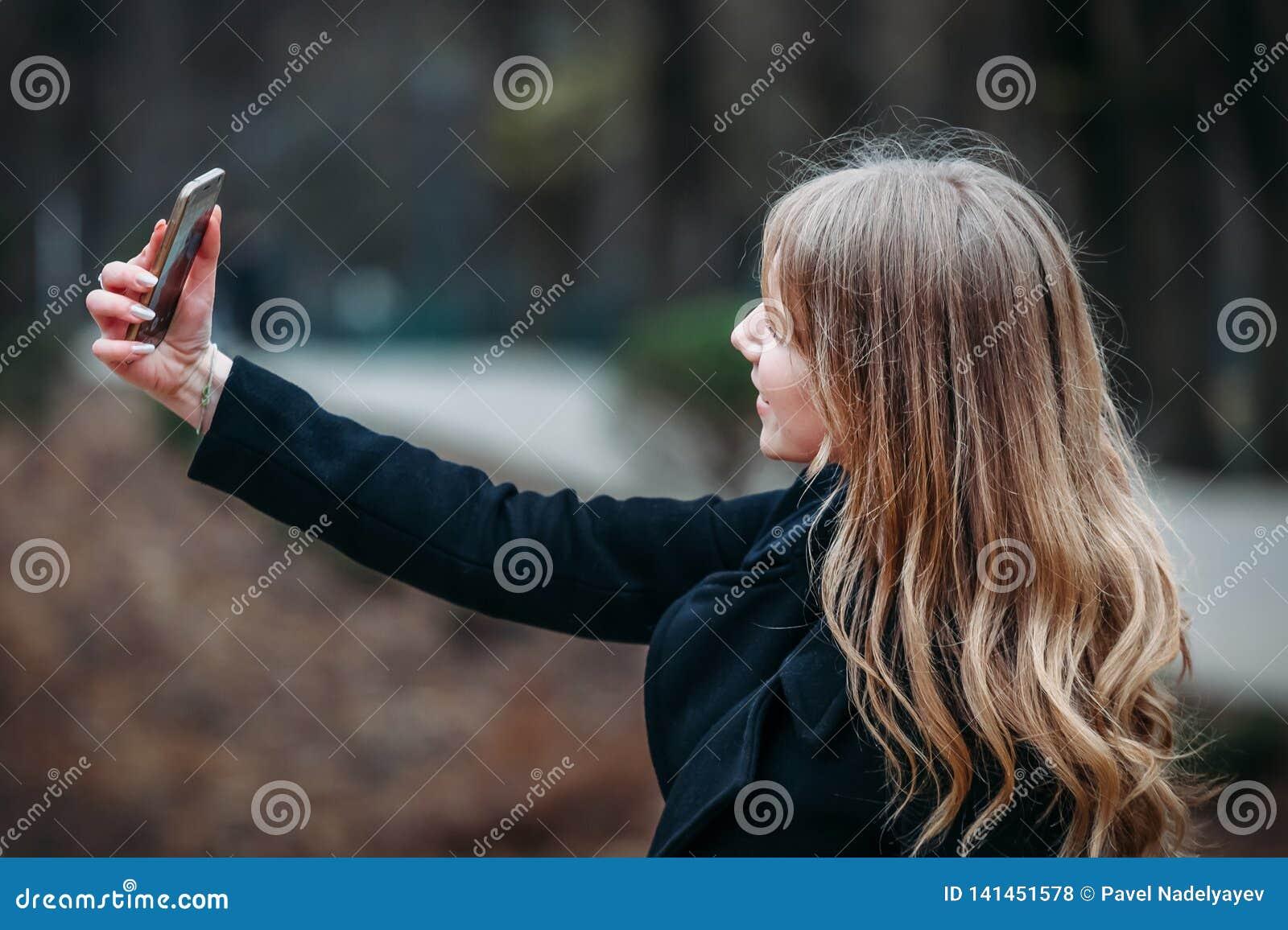 Utomhus- stående av en långhårig kvinna för romantisk nätt elegant affär som tycker om en promenad till och med staden med en tel